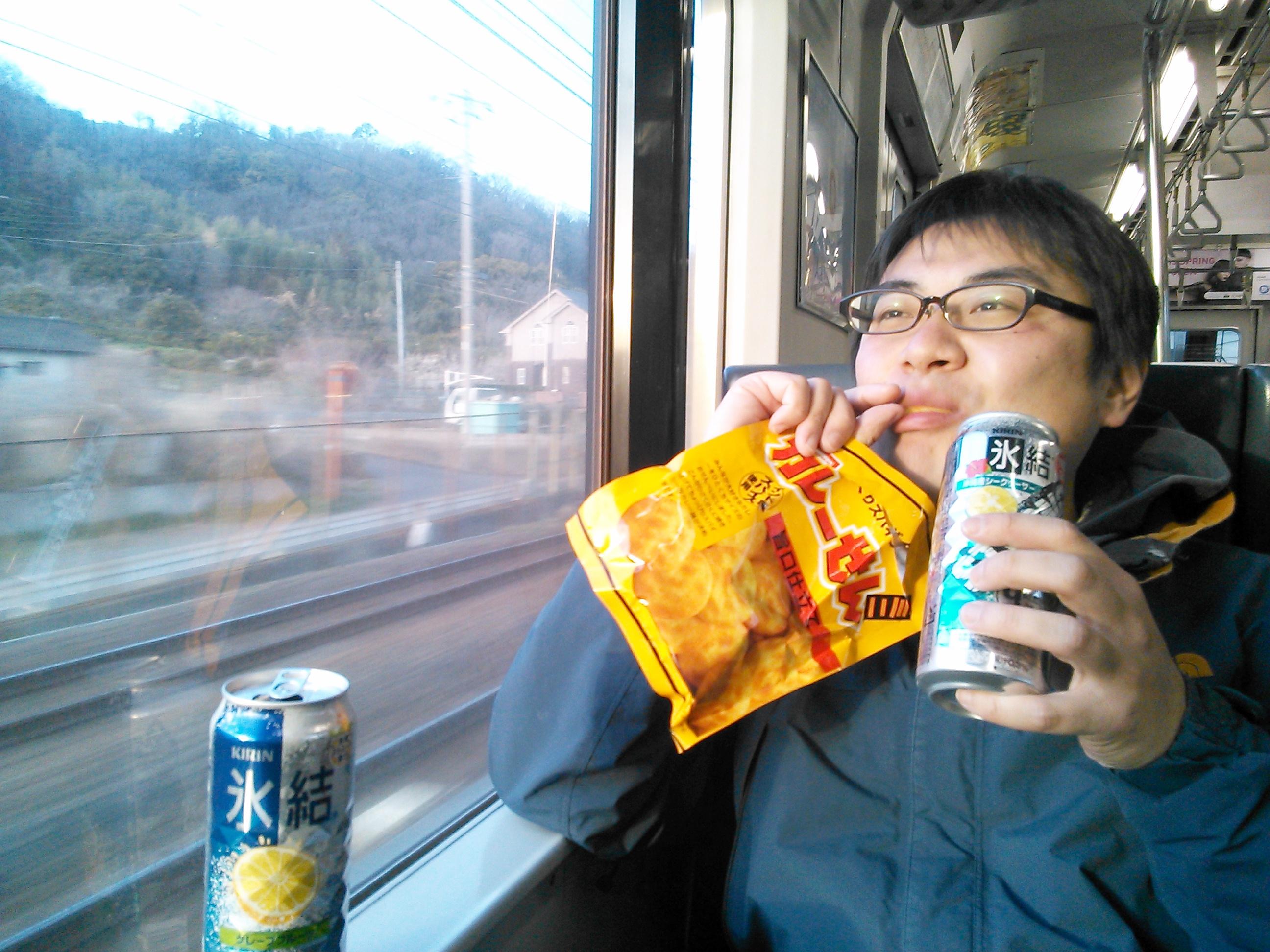 電車内でカレーせんをつまみに酒を飲む佐藤オキアミ