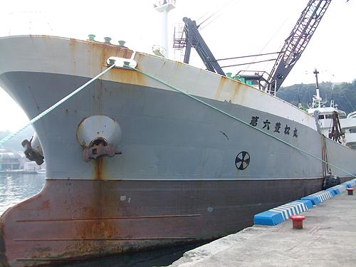 真鶴港の堤防に停泊する巨大な石積み船